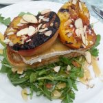 Appetizer of the evening: grilled peach over warmed brie and arugula, drizzled with honey & almo