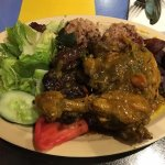 Curry chicken with oxtails, red beans and rice, plantains, and salad