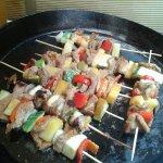 Pinchitos asados de cerdo con coco y vegetales.