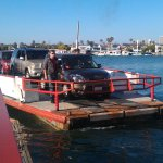 The three-vehicle ferry boat approaching the Balboa Peninsula with Balboa Island in the backgrou