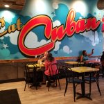 "Vibrant full wall mural just inside entrance invites guests to ""Eat Cuban."""