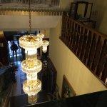 Las escaleras al primer piso con una gran lámpara