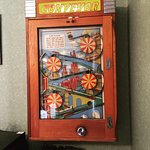 Vertical pin ball machine in the dining room. You need 1d coins