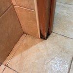 Dirty floor tiles and rotten door jam