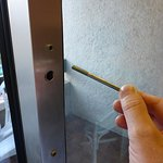 An old bolt through a hole in the door. The only way to lock the patio door in a guest bedroom.