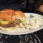 Large cheeseburger on homemade bun; potato salad