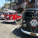 Classic Volkswagon Vans line up on Main Street during Surf City Days