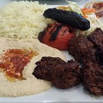 Beef kabob with a side of rice, humus, salad, and a grilled tomato and pepper.