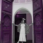 La Carmina in her 5-star Marrakesh riad, with giant Moroccan doors and tiles.