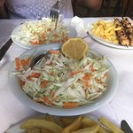 Cabbage salad in the middle, souvlaki chicken plate in the top right corner