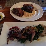 Breaded pork chops with cheese grits and local greens (top) quail with risotto cake and greens