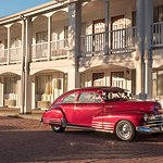 Guests classic car parked by room.
