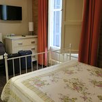 Habitación con balcón y cama matrimonial.