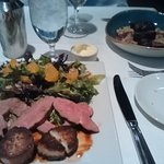 Right: Pan Seared Venison Front: scallops, duck and salad with citrus and hazelnuts