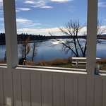 Cabins have covered patios that look out on the lake.