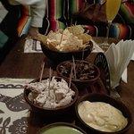 tabla de carne , pollo , quesos y nachos con salsa verde.