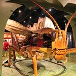 The giant grasshopper with an electric train under it.