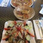 Salat mit Putenstreifen und hauseigenem Dressing und eine Pizza.