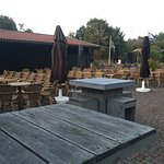 Seating area next to restaurant. Note clay pigeon range in background