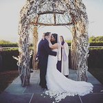 Our first kiss as husband and wife in front of the spectacular pergola in the ceremony garden