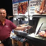 Manuel prepares sea bass on the BBQ right on the boardwalk