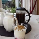 Would you like coffee or tea? Fruit on the bottom yogurt with granola.