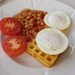 Delicious English breakfast with potato waffle.