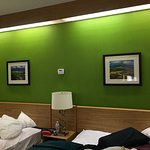 I do like the green accent wall with pastoral, colorful art prints