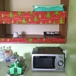 Microwave contained old food from previous people, only 1 cup, old xmas paper covering shelves.