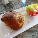 Popover containing scrambled eggs and cheese, served with a fruit salad