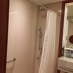 """Shower is """"sunken"""" and has grab bar, adjustable hand sprayer and monsoon ceiling shower head."""