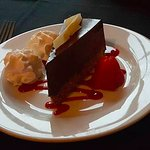 Chocolate torte with raspberry coulis, strawberry and whipped cream