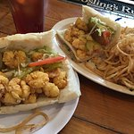 One large Shrimp Po Boy split on two plates with Fried Onion Rings