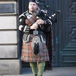 Bagpiper dressed in traditional Scottish kilt playing in the street.
