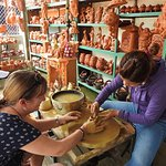 Being shown how to do the pottery wheel by a beautiful villager