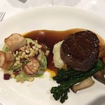 Delicious filet mignon on a bed of mash and sautéed local mushrooms served with seared scallops
