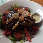 steak and prawns on a bed of salad
