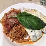 Chicken Parmigiana with spaghetti topped with their signature basil leaf