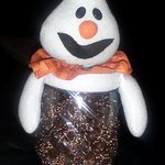 a ghost on a mason-type jar for Halloween filled with chocolate-covered pretzel nuggets