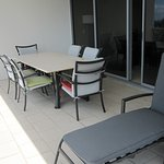 Balcony outdoor 6-seat setting, plus recliner lay lounge.