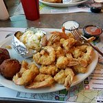 Fried shrimp platter with loaded baked potato and hush puppies