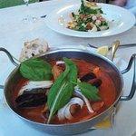 Seafood tomato based soup and mixed fish salad dish