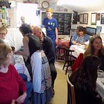 Inside the tea room. Caroline (the owner) has the long apron, with her back to us.