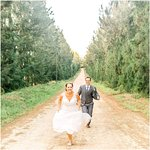 A fun photo of a wedding couple running up the main entrance