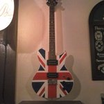 Electric guitar finished with British flag hanging on wall.