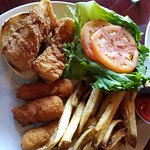 Fried cod sandwich with hush puppies and fries.