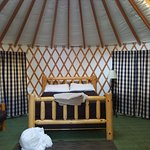 Inside of yurt (sheets piled on the floor after stripping the bed)