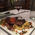 NY strip garnished with blood oranges atop, mashed chunky potatoes & coconut hash.