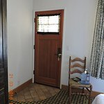 entry door next to the chiar. and you can see bed and tv cabinet.