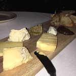 Cheese board with fresh honeycomb, fig jam, and baguette slices.